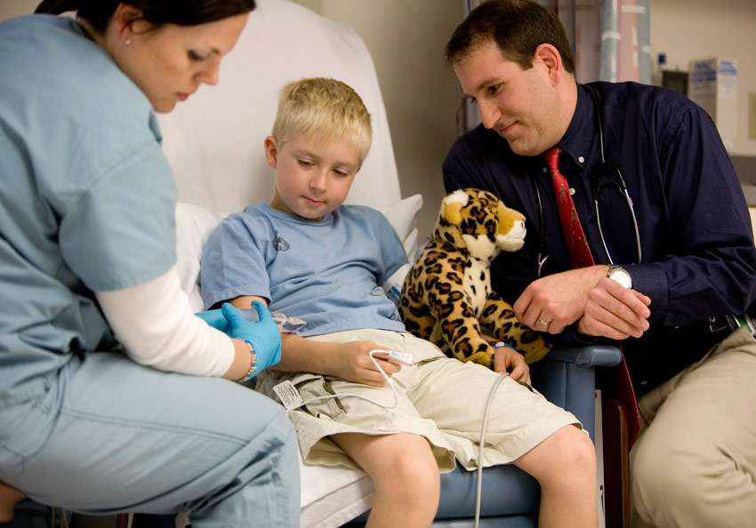 Dr. Haller showing a young patient a stuffed animal