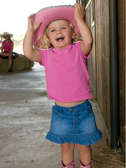 Little girls in a pink shirt and matching cowgirl hat