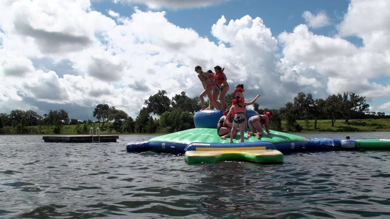 Group of kids jumping off a large float in the middle of a lake