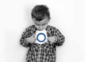Little boy pulling back buttoned shirt to reveal a white shirt with a blue circle