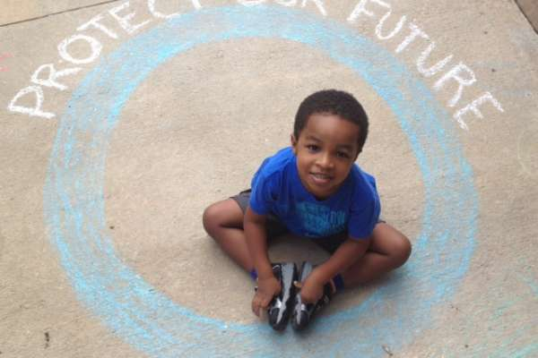 Boy sitting on pavement inside a blue circle drawn in chalk with text reading protect our future