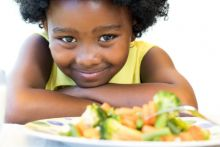 Young girl looking at a plate of vegetables