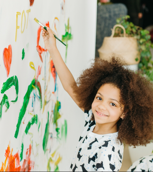 Young girl painting on a wall