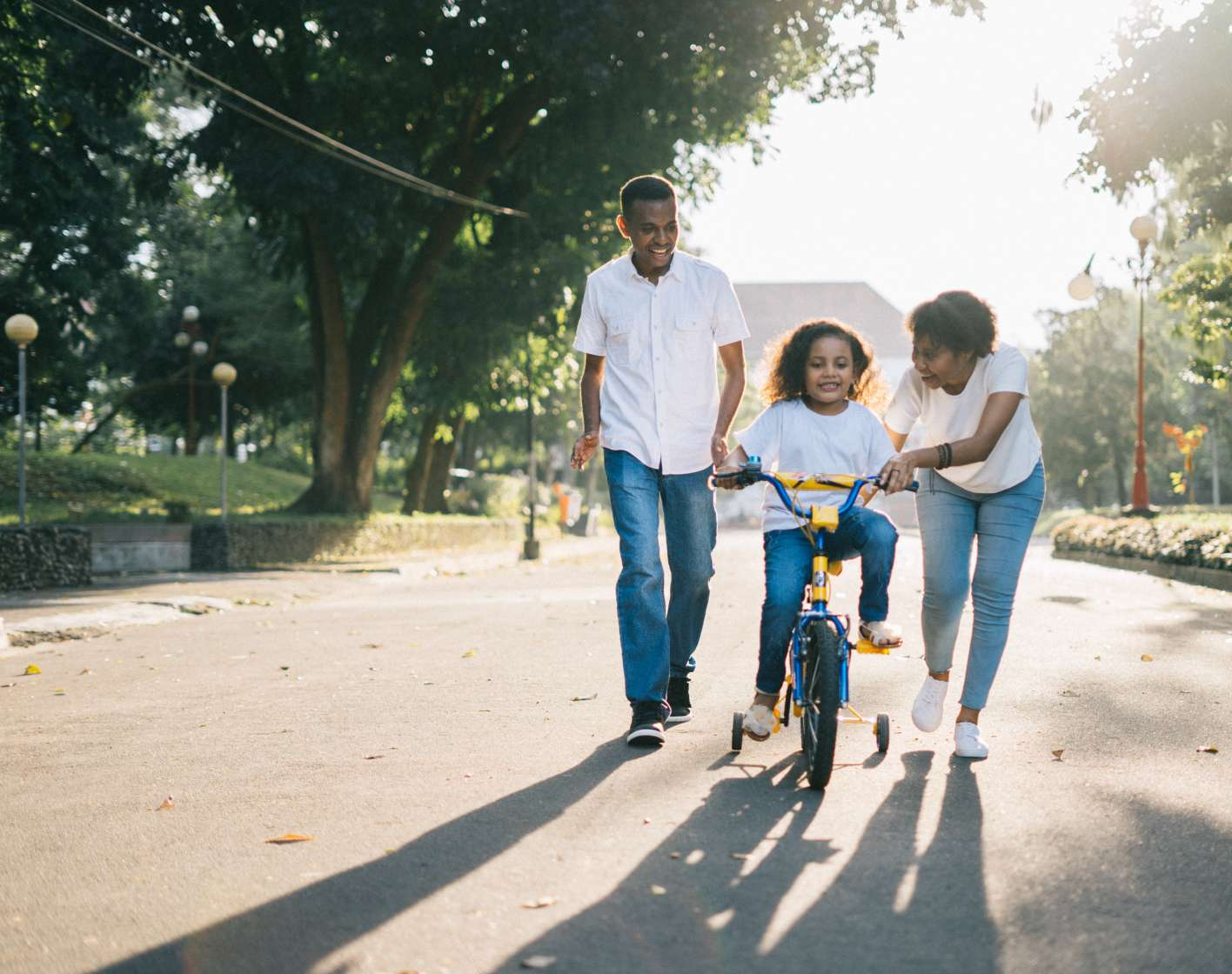 Two adults helping a child learn how to ride a bicycle