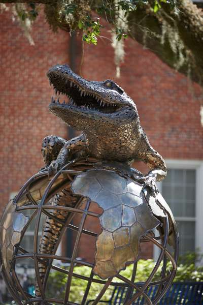 Statue of gator sitting on a globe